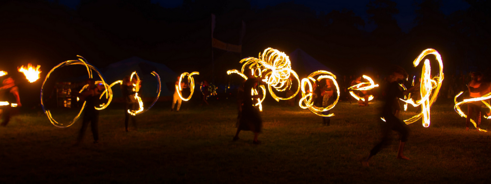 A group of fire-dancers weaving patterns of light in the dark